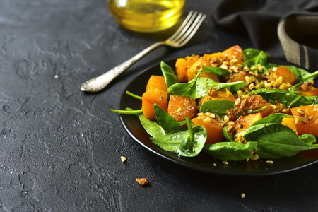 Roasted pumpkin salad with spinach and walnut on a black plate on a stone background.Space for text. Stock Photo