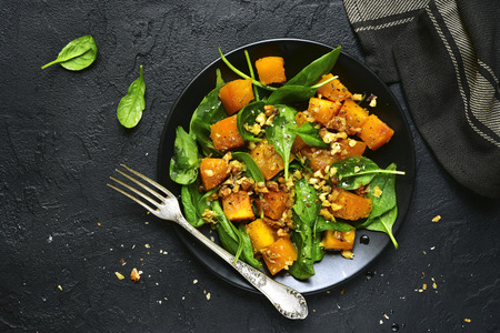 Roasted pumpkin salad with spinach and walnut on a black plate on a stone background.Top view. Archivio Fotografico