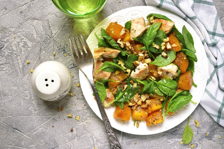 Pumpkin stew with chicken,spinach and walnuts on a white plate on a grey concrete or stone background.Top view.