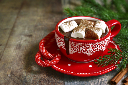 comfort food: Homemade spicy christmas hot chocolate with marshmellow  in a red cup on a rustic wooden background. Stock Photo