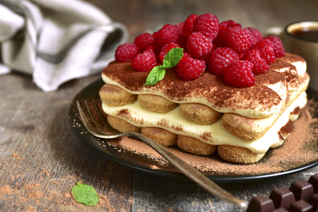 Tiramisu with raspberry on a black plate on a rustic wooden background.