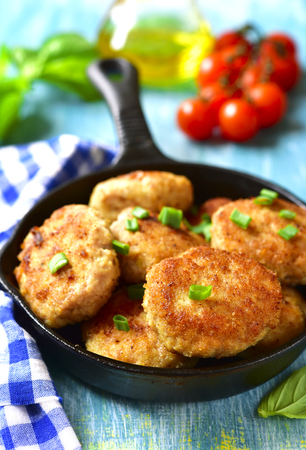 Chicken cutlets in a skillet on a blue wooden background. Archivio Fotografico