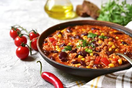 Chili con carne in een kleikom op een concrete of steen-traditionele schotel als achtergrond van Mexicaanse keuken.