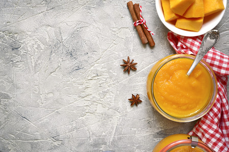 meatless: Pumpkin puree in a glass jar on a grey concrete or stone background.Top view. Stock Photo