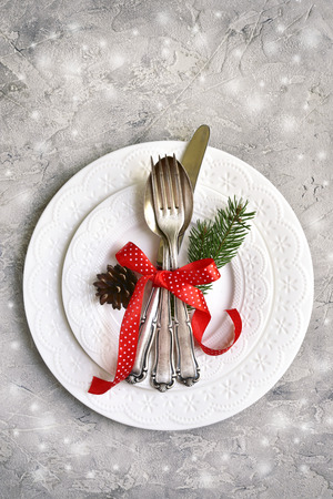 Christmas table place setting with christmas pine branches and plates, kine, fork and spoon.Christmas holiday background.Top view. Stock Photo