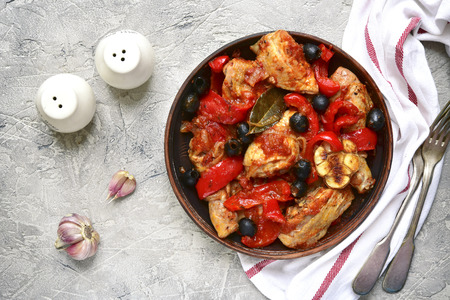 Chicken stewed in tomato sauce with bell pepper,onion and olives in a clay bowl on a grey concrete,stone or slate background.Top view.