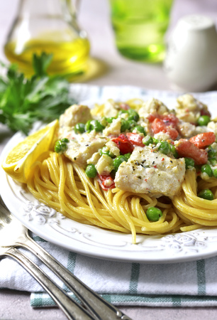 Codfish in a cream sauce with vegetables garniched with spaghetti on a concrete,stone or slate background. Stock Photo