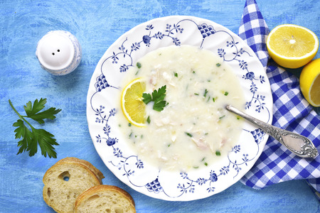 Avgolemono - traditional greek chicken soup with rice,lemon and eggs on a blue background.Top view.
