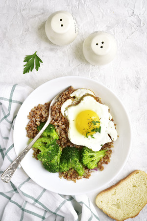 Buckwheat with fried egg and broccoli for a healthy breakfast.Top view. Stock Photo
