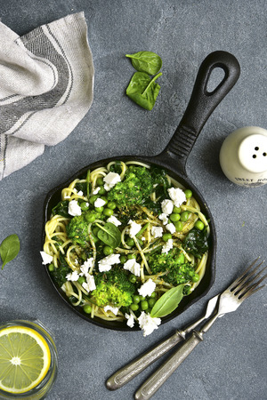 Spaghetti primavera with green spring vegetables and feta cheese in a skillet on a grey concrete,stone or slate background.Top view.