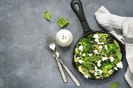 primavera: Spaghetti primavera with green spring vegetables and feta cheese in a  skillet on a grey concrete,stone or slate background.Top view with copy space. Stock Photo