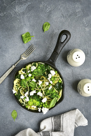 primavera: Spaghetti primavera with green spring vegetables and feta cheese in a  skillet on a grey concrete,stone or slate background.Top view. Stock Photo