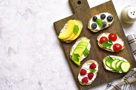 Assortiment van fruit en plantaardige toosts met ricotta op een houten scherpe raad op lichte beton, steen of leiachtergrond Hoogste mening.