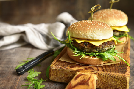 Cheeseburger with mushroom cutlet and arugula on a cutting board on a rustic wooden background. Stok Fotoğraf