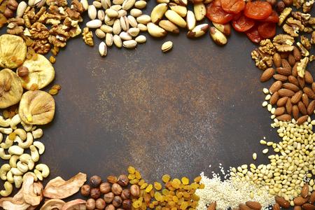 Assortimento di noci, frutta secca e semi su uno sfondo arrugginito di metallo.Concept di snack sano, vista dall'alto con spazio per il testo.
