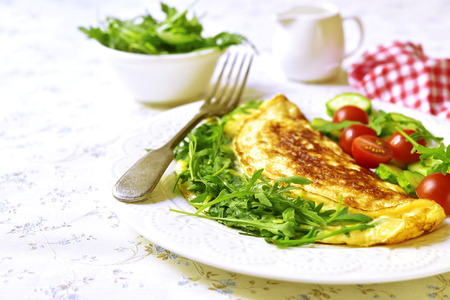 Omelet with cheese and arugula - healthy diet breakfast on white plate on light background.