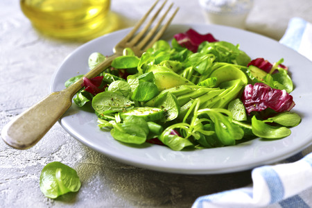 De salade verlaat mengeling met avocado en komkommer op een plaat op een grijze steen, lei of concrete achtergrond. Stockfoto
