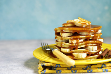 Banana pancakes with caramel for a breakfast on a yellow plate on a blue backcground.