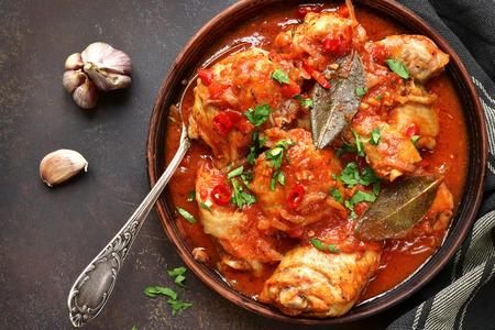 Chakhokhbili - steelt hutspot met koriander (peterselie) in tomatensaus in een kleikom, traditioneel gerecht van Georgische keuken. Hoogste mening met exemplaarruimte. Stockfoto - 74183065
