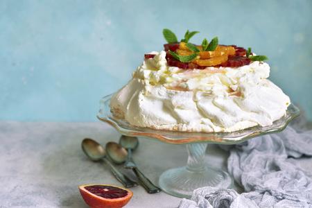 Meringue cake Pavlova with orange and citrus syrup on a slate,stone or concrete background. Stock Photo