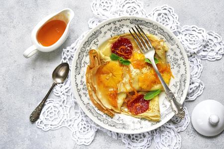 Zelfgemaakte crêpes suzette - traditionele Franse dunne pannenkoeken met oranje siroop op een lichte lei, steen of concrete achtergrond. Bovenaanzicht.