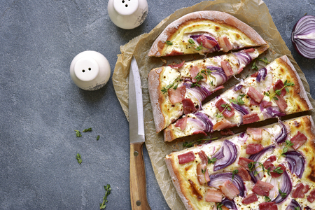 Tarte flambee - traditional rustic french pie with onion and bacon.Top view.