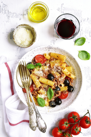 macarrones: Tortiglioni bolognese with tomato cherry and black olives in a craft bowl on a white slate,stone or concrete background.Top view.