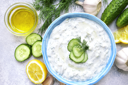 Tzatziki - yoghurt sauce with cucumber and dill on a light slate or stone background,traditional greek cuisine.Top view .