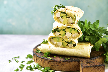 Chicken avocado burritos on a wooden cutting board on light blue slate background. Archivio Fotografico