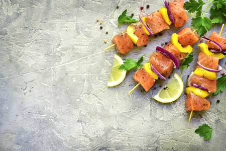 Raw salmon kebab on a grey slate,stone or concrete background.Top view with copy space. Stock Photo