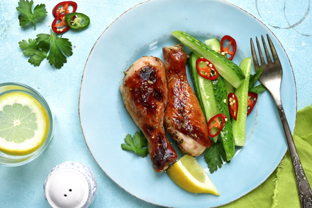 Roasted chicken drumctick with spicy cucumber salad on a turquoise slate,stone or concrete background.Top view. Stock Photo - 79768362