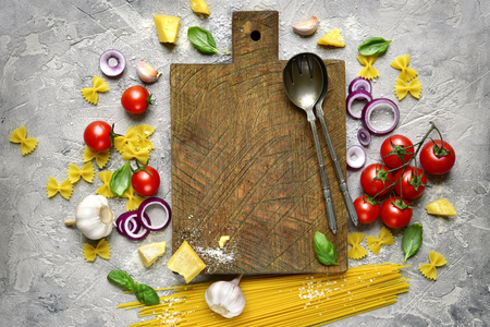 Traditional ingredients of italian cuisine : pasta,cheese and assortment of vegetables on a grey slate,stone or concrete background.Top view with copy space. Archivio Fotografico