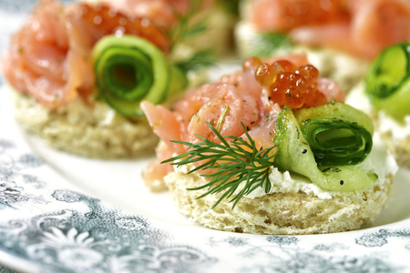 Canape with salmon,cucumber and red caviar on a curd spread on a light slate,stone or concrete background.