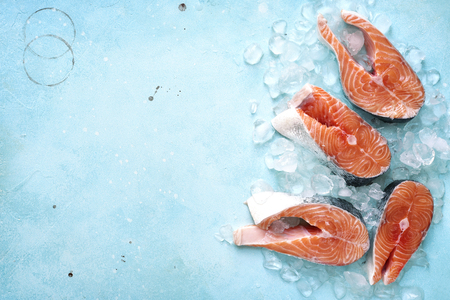Bistecche di salmone crudo su ghiaccio su uno sfondo blu ardesia, pietra o metallo. Vista dall'alto con lo spazio per il testo.