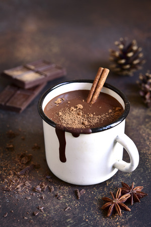 Homemade spicy hot chocolate with cinnamon in enamel mug on a slate,stone or concrete background. 版權商用圖片