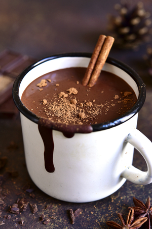 Homemade spicy hot chocolate with cinnamon in enamel mug on a slate,stone or concrete background. Stock fotó