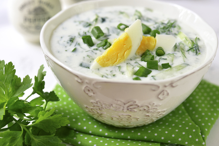 Summer cucumber cold soup with greens and boiled eggs in a white bowl on a light slate,stone or concrete background.