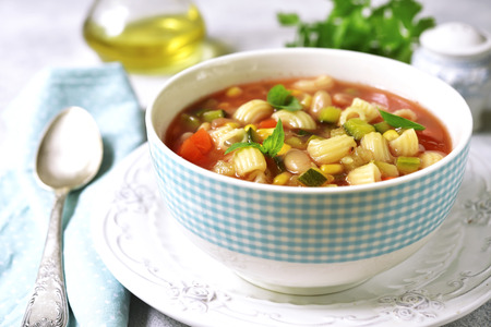 Minestrone - traditional italian vegetavle soup in a bowl on a light slate,stone or concrete background. Stockfoto