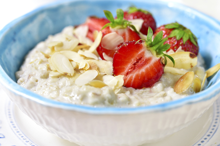 Oat porridge with fresh strawberry in a blue bowle on a light slate,stone or concrete background for a breakfast. Stock Photo