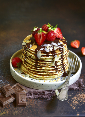 Homemade pancakes with fresh strawberry,chocolate and almond petals on a dark slate,stone or concrete background.Rustic style. Archivio Fotografico