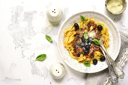 meatless: Tagliatelle with eggplants and tomato sauce in a rustic bowl on a light slate,stone or concrete background.Top view. Stock Photo