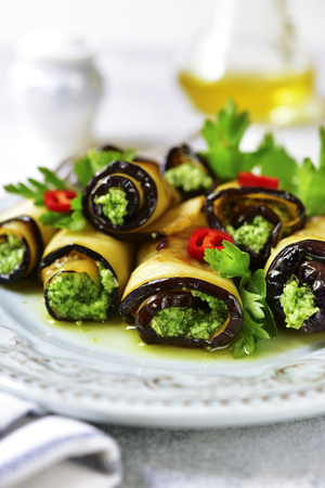 Eggplant rolls with basil pesto on a plate on a light slate,stone or concrete background.