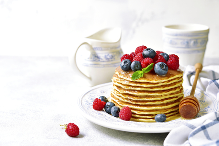platanos fritos: Homemade pancakes with honey and fresh berries on a light slate,stone or concrete background.