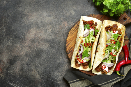 Mexican tacos with pulled beef,fresh cucumber and yogurt dressing on a cutting board over dark slate,stone or metal background.Top view with copy space.