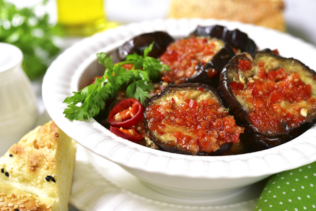 Eggplant slices in a spicy red sauce in a clay bowl over light slate,stone or concrete background. Stock Photo