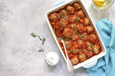 Meatballs stewed with carrot and onion in tomato sauce on a light slate,stone or concrete background.Top view. Foto de archivo