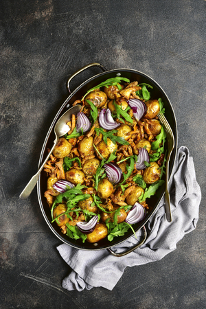 Oven baked new potato with mushrooms,onion and arugula in a pan over dark slate,stone or metal background.Top view.