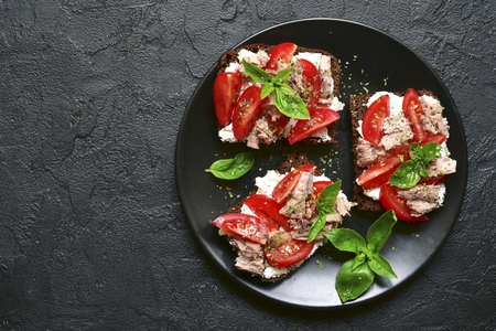 Rye sandwich with tomato,feta and tuna fillet on a black plate over dark slate,stone or concrete background.Top view with space for text. Banco de Imagens