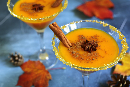 Pumpkin cocktail in a martini glasses on a blue slate,stone or concrete background.