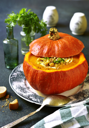 Pumpkin soup with walnuts and chickpea in a pumpkin on a dark green slate background.Rustic style.